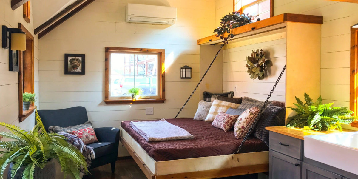 tiny home bedroom with window and bed folded down from the wall with pillows and a throw blanket on it nicely made.