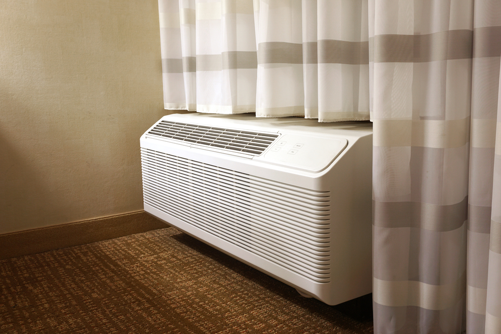 PTAC air conditioning unit with fitted curtains draped around it